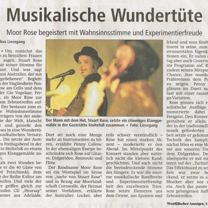 "CULTURE AT THE CROSSWALK, BÖNEN (GERMANY) 14/10/2013  Westfälische Anzeiger – by Markus Leisegang  ""GIVEN THE APPLAUSE AND THOROUGH ENJOYMENT…HE CHARMS OUT OF HIS MAGICAL MUSIC BOX.""  [TRANSLATION] ""A MAGICAL MUSIC BOX OF SURPRISES: [THE] MOOR ROSE ENTHUSES WITH HIS EXCEPTIONAL VOICE AND FUN FOR THE EXPERIMENTAL""   ""First we start with a cliche: women would say that Stuart Rose gives them goose bumps with his voice. What would one say to the Australian with his 'borrowed' duo, the English Penny Callow on cello and the Dutch Gio Vogelaar, percussion, when (The) Moor Rose played at the ""Culture at the Crosswalk""? He was certainly admired by them with the amazing voice of the hat wearer from the other side of the globe, given the applause and thorough enjoyment of the different musical set pieces he charms out of his magical music box.  The Australian puts them together in the Gaststätte Stoltefuß on Friday evening and creates a beautiful musical painting. More than two hours he inspired guests of Reinhard Potschinski, the creator of culture at the Culture at the Crosswalk concert series. Many guests went straight to grab the ""Hearsay"" CD off the man from Adelaide. Penny Callow said you can hear a lot more instruments on the CD. In the former pub, Rose focused on guitar, didgeridoo, bouzouki and flute at this gig.  The band name (The) Moor Rose, so explained the Australian, is not supposed to be a pun like 'more of Stuart Rose' but is in reference to the Moor landscapes of Cornwall, the home of his ancestors. The easy going, but often hard to understand due to a strong accent – Rose moderated the evening. This Friday the little anecdotes weren't of course the centerpiece of the concert. Also the impressive voice of the singer neither. It was the enormous musical diversity and the joy with which the excellent trio experimented. Rose included oriental elements as well as from Spain, Ireland and the fifth continent into his own compositions. Rose allowed his musical team members to show their own preferences to the audience. Penny Callow shone in her duet with Vogelaar playing a fast Tango- variation..  Rose allowed him-self some soloist excursions. He demonstrated his free spirit while playing. At the beginning of the concert he was playing by himself. Far away from the usual traditional Folk Music handiwork, he focused in a very expertly way on the technique of sampling: He started with a melody line in sonorous tones with the didgeridoo, while he recorded the loop, over which he played the ""Turkish flute"". The effects board at his feet was impressive but he only used it sparingly, as a good musician does. That too fitted in with this successful concert at the Crosswalk."""